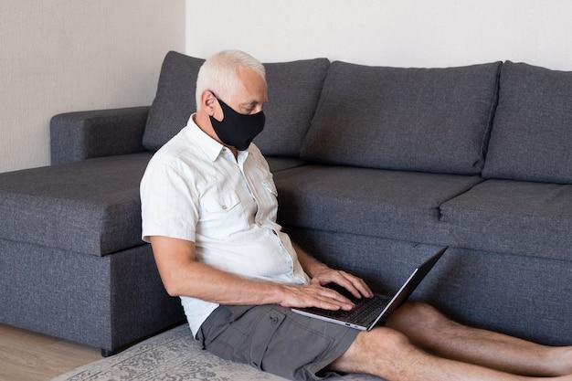 Старший мужчина, работающий на компьютере дома в маске