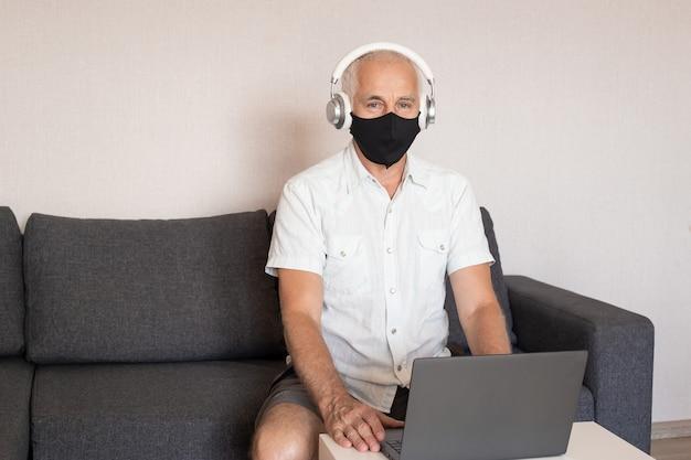 마스크를 쓰고 집에서 컴퓨터에서 작업하는 수석 남자