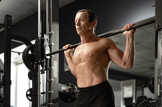スクワットをしているジムで運動している年配の男性