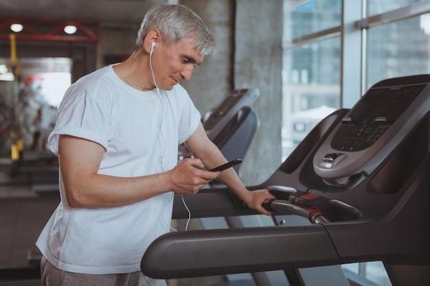 Старший мужчина работает в тренажерном зале