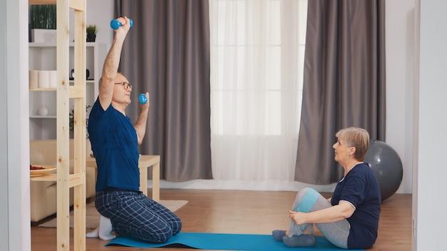 治療中にダンベルで運動する年配の男性。在宅支援、理学療法、老人の健康的なライフスタイル、トレーニング、健康的なライフスタイル