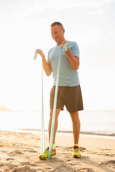 Старший мужчина работает с эластичной веревкой на пляже