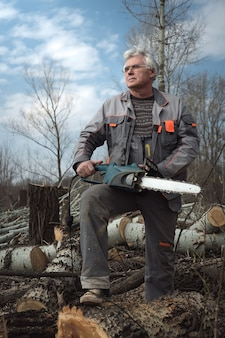 Senior man working with a chainsaw.
