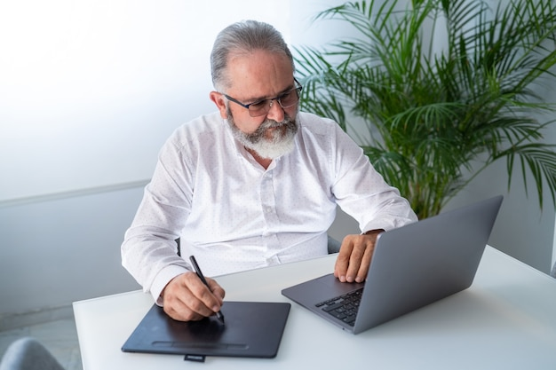 그의 사무실에서 노트북 및 태블릿을 사용하는 수석 남자
