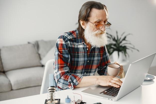 居間でラップトップで働く年配の男性
