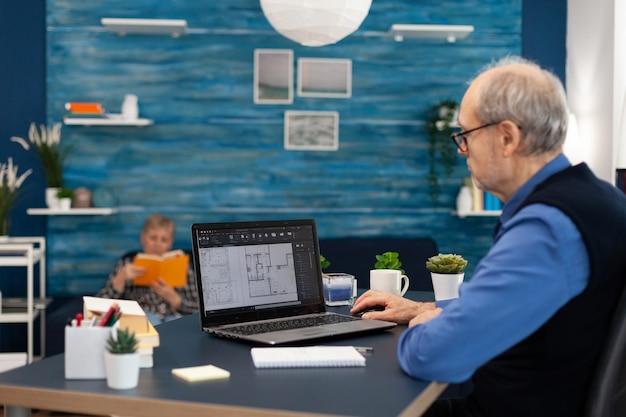 집 계획을 세우기 위해 노트북으로 작업하는 시니어 남자는 경험이 풍부한 건설 엔지니어 디자이너가 ...
