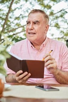年配の男性が彼の日記を書く