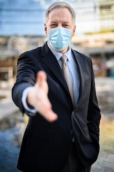 Covid19に対して屋外で保護マスクを着用して握手を与えるシニアマネージャー