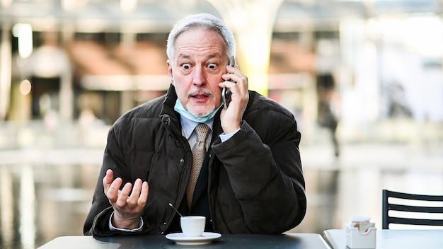 屋外でコーヒーを飲みながら電話に腹を立て、コロナウイルスから保護するために顎にマスクを付けているシニアマネージャー