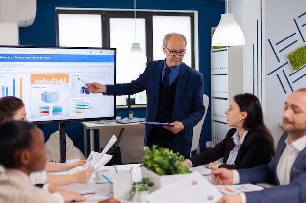 会議室説明会で説明するビジネス研修を行う上級管理職