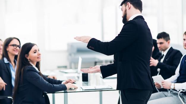 회사의 선임 관리자는 현대 사무실에서 비즈니스 팀과 작업 회의를 개최합니다.