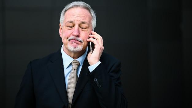 がっかりしたり動揺したりしている電話の上級管理職