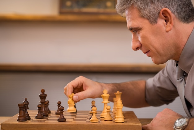 Старший менеджер играет в шахматы в офисе. зрелый деловой человек обдумывает свой следующий ход в шахматы. лидерство наслаждается своим следующим ходом в шахматы. стратегия и концепция управления.