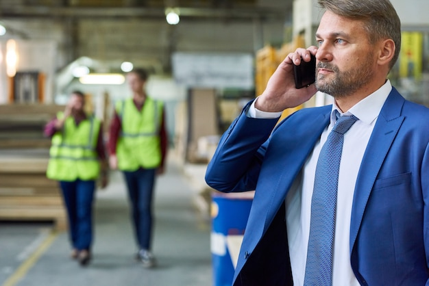 Senior manager speaking by phone at factory