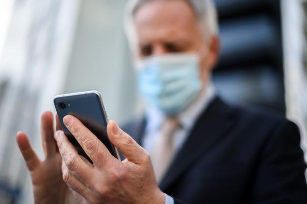 코로나 바이러스 전염병으로부터 보호하기 위해 마스크를 쓰고 야외에서 스마트 폰을 사용하는 고위 관리자