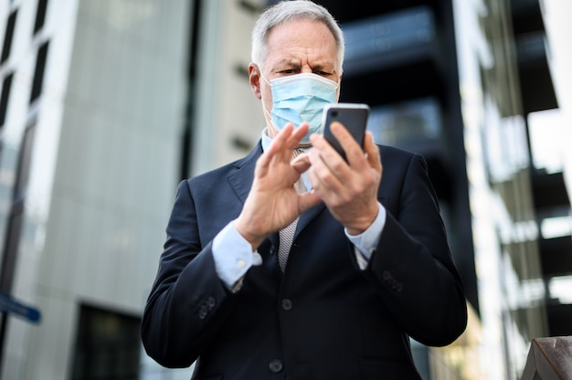 코로나바이러스 전염병으로부터 보호하기 위해 마스크를 쓰고 야외에서 스마트폰을 사용하는 고위 관리자