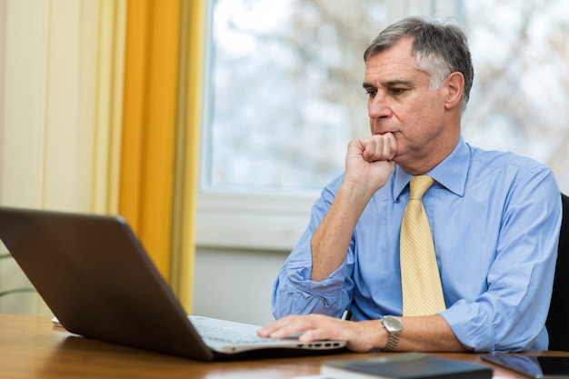 Senior manager at work on his laptop in his office