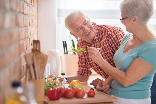 Matrimonio senior che cucina insieme pasto sano