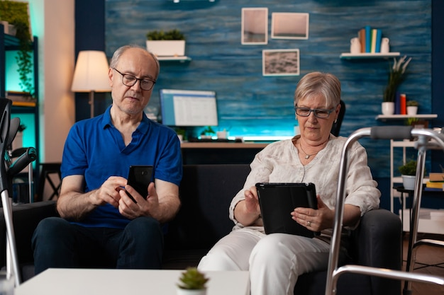 Senior married couple using smartphone and tablet