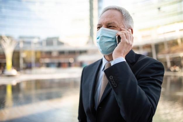 パンデミック・パンデミックの最中に都市で電話で話しているマスクされたシニアビジネスマン