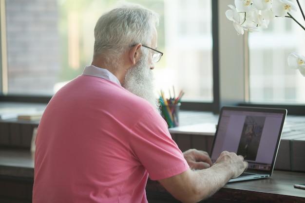 Старший зрелый деловой человек с кофе в кафе и работает на своем ноутбуке