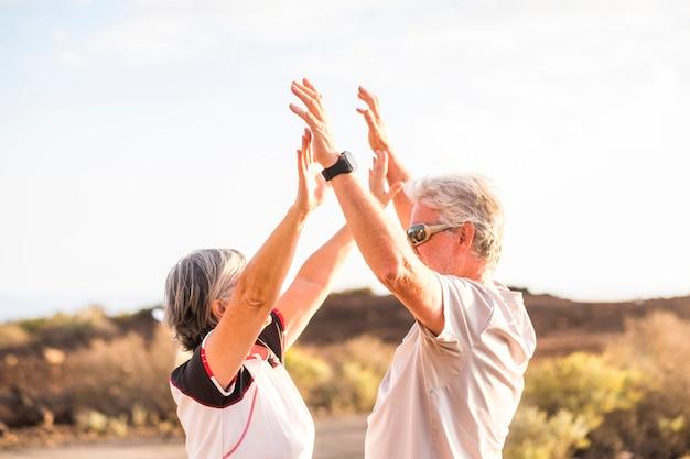 수석 성숙한 부부는 여름에 좋은 날씨의 날 아래에서 5를주고 포옹을 함께 즐기고 승리합니다. 스포츠 활동 및 옷. 활동적인 노인과 행복 개념