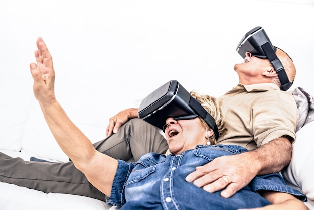 Senior mature couple having fun together with virtual reality headset sitting on sofa