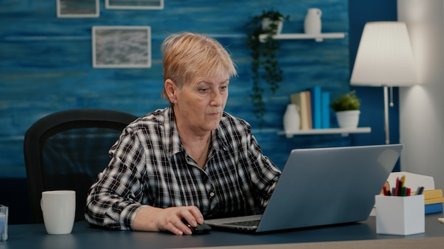 Senior mature older woman watching business training, online webinar on laptop computer remote working, reading, analysing statistics from home. old retired businesswoman typing, writing project