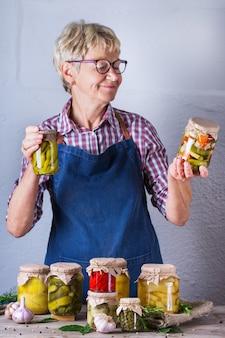 수제 보존 및 발효 식품이 담긴 항아리를 들고 있는 성숙한 여성. 다양한 절인 야채와 절인 야채. 가사, 가정 경제, 수확 보존