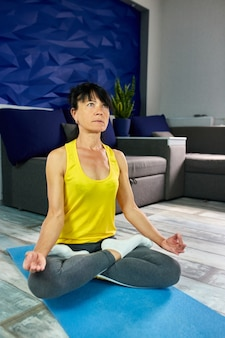 ヨガマットの上に蓮華座に座って、自宅の居間でストレッチ運動をしている年配の成熟した女性。健康的なライフスタイルのコンセプト。