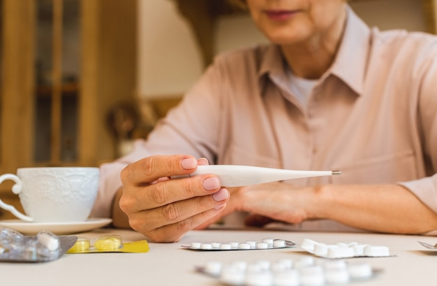 집 부엌에서 의료 온도계로 체온을 측정하는 알약을 든 중년 여성. 감기와 독감, 코로나바이러스 covid-19 클로즈업 개념.