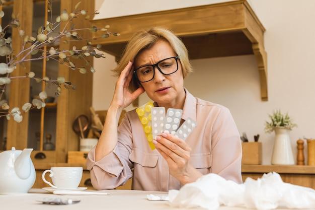 집 부엌에서 의료 온도계로 체온을 측정하는 알약을 든 중년 여성. 감기와 독감, 코로나바이러스 covid-19 개념.