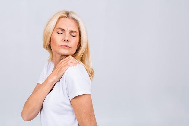 Старшая зрелая женщина с болью в плече, изолированная на белой предпосылке.