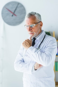 Senior medical practitioner thinking in office
