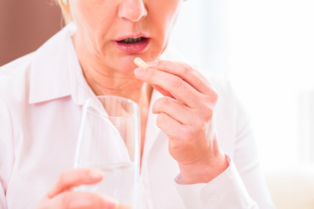 Senior medicate with pills at home