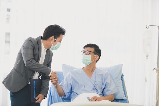 Старшие мужчины лежали на кровати на встрече в больнице с финансовым советником, пожилой женщиной, читающей контракт. оба были в гигиенических масках, чтобы предотвратить вспышки заболеваний.