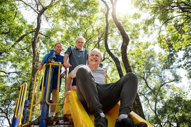 Senior men playing at a playground slide