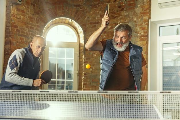 직장에서 탁구를 치는 노인들. 캐주얼한 옷을 입은 친구들은 화창한 날에 함께 탁구를 칩니다. 여가 활동, 스포츠, 우정, 팀 빌딩, 팀워크의 개념.