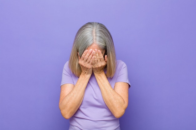 Senior or middle age pretty woman feeling sad, frustrated, nervous and depressed, covering face with both hands, crying