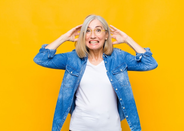 Senior or middle age woman feeling stressed, worried, anxious or scared, with hands on head, panicking at mistake