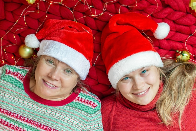 Senior mom and her adult daughter in santa hats lie on a soft hand knitted merino wool blanket. mother and daughter are friends. having fun, loving family