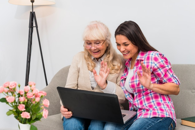Senior mother and adult daughter waving their hands while video chatting on laptop