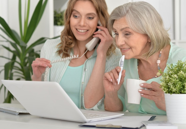 Senior mother and adult daughter working with laptop together