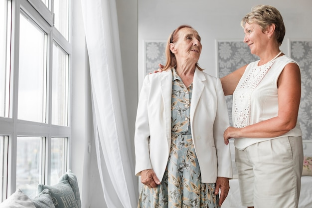 Senior mother and daughter looking at each other while standing near window