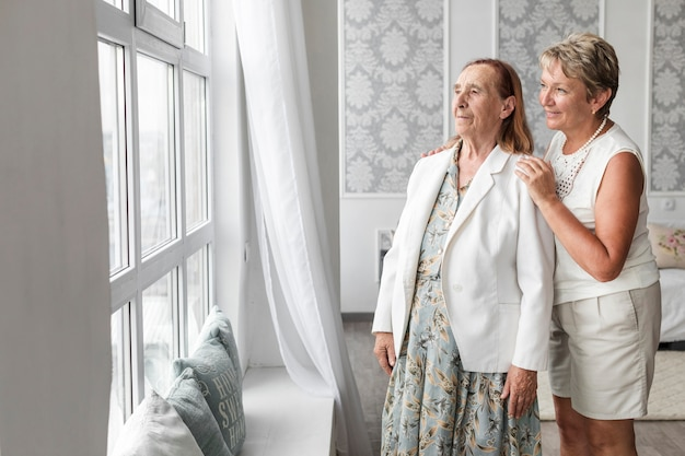 Senior mother and daughter looking through window at home