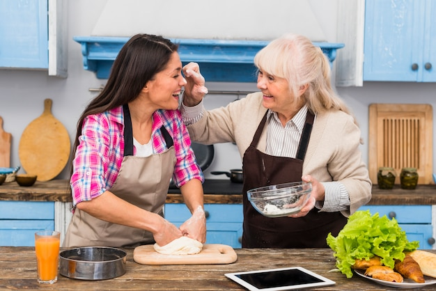 Senior mother and her daughter making fun while kneading the dough
