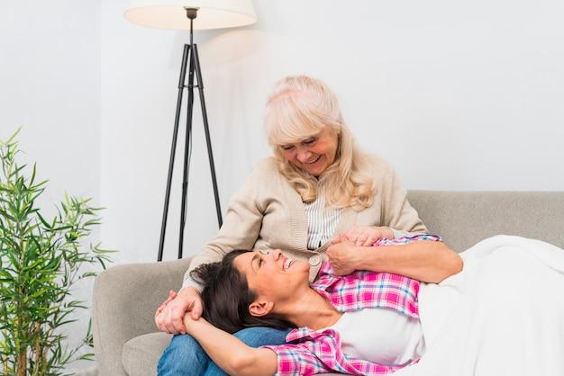 彼女の膝の上に寝ている彼女の大人の娘を見て年配の母親