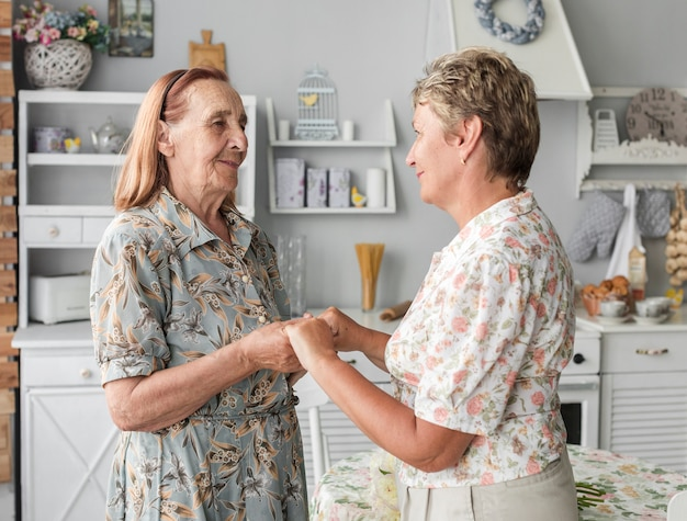 Senior mother and mature daughter holding hand together in kitchen