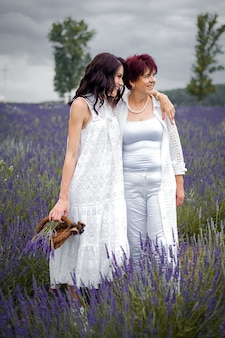 Senior mother with adult daughter walking on the lavender field