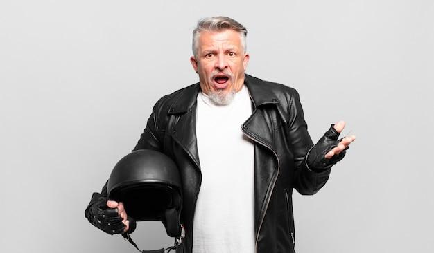 Старший мотоциклист чувствует себя чрезвычайно шокированным и удивленным, встревоженным и паническим, с напряженным и испуганным взглядом